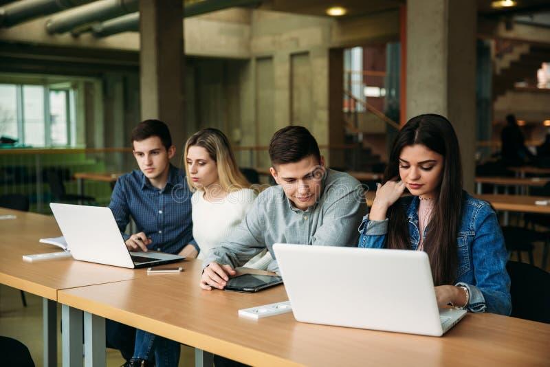 El grupo de estudiantes universitarios que estudian en la biblioteca escolar, una muchacha y un muchacho están utilizando un orde fotografía de archivo