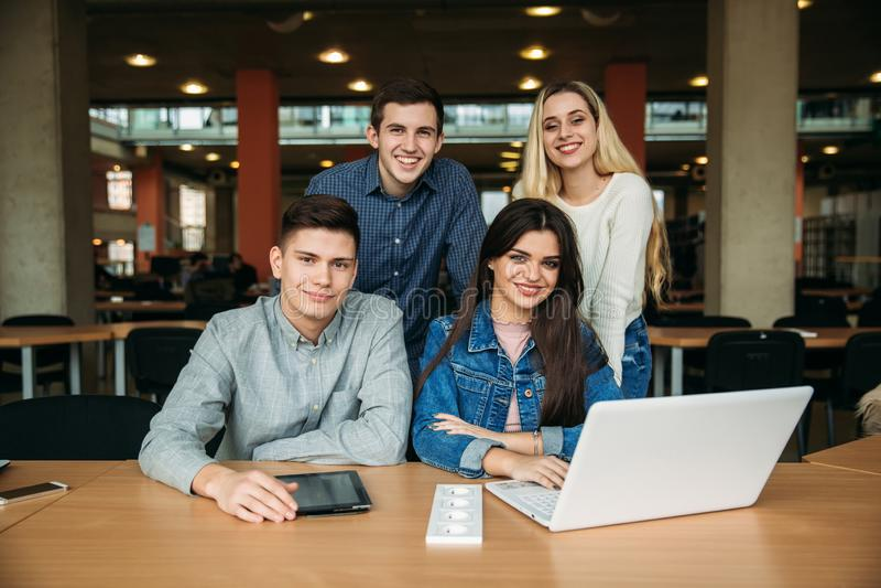 El grupo de estudiantes universitarios que estudian en la biblioteca escolar, una muchacha y un muchacho están utilizando un orde foto de archivo libre de regalías