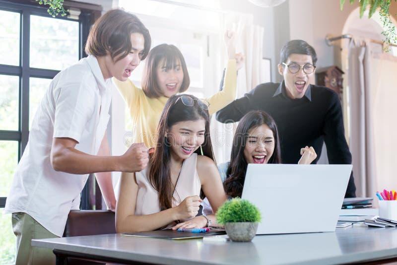 El grupo de freelancers acertados está celebrando trabajando junto sentarse en espacio coworking imagen de archivo libre de regalías