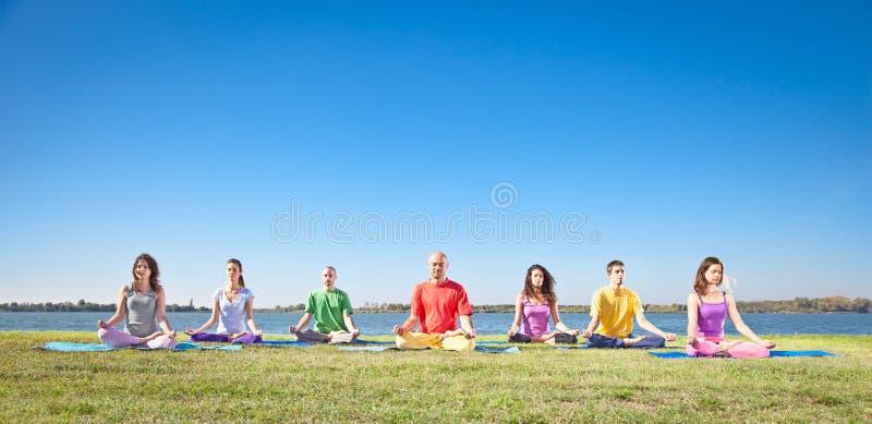 El grupo de gente joven tiene meditación fotos de archivo