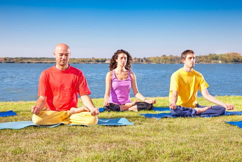 El grupo de gente joven tiene meditación en clase de la yoga fotos de archivo libres de regalías