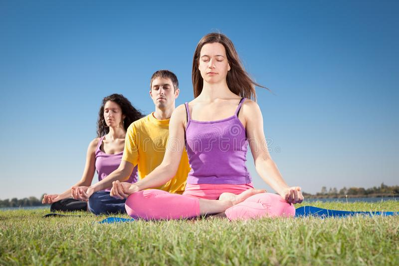 El grupo de gente joven tiene meditación en clase de la yoga imágenes de archivo libres de regalías