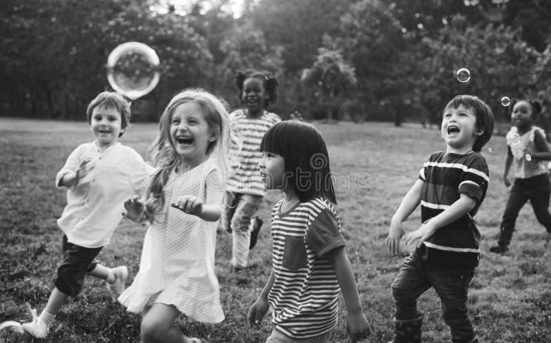 El grupo de guardería embroma a los amigos que juegan la diversión de las burbujas que sopla foto de archivo