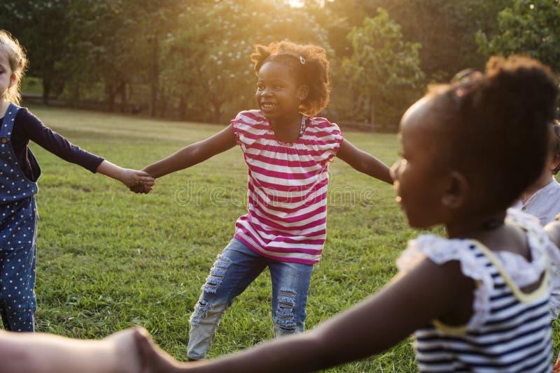 El grupo de guardería embroma a los amigos que llevan a cabo las manos que juegan en el parque foto de archivo