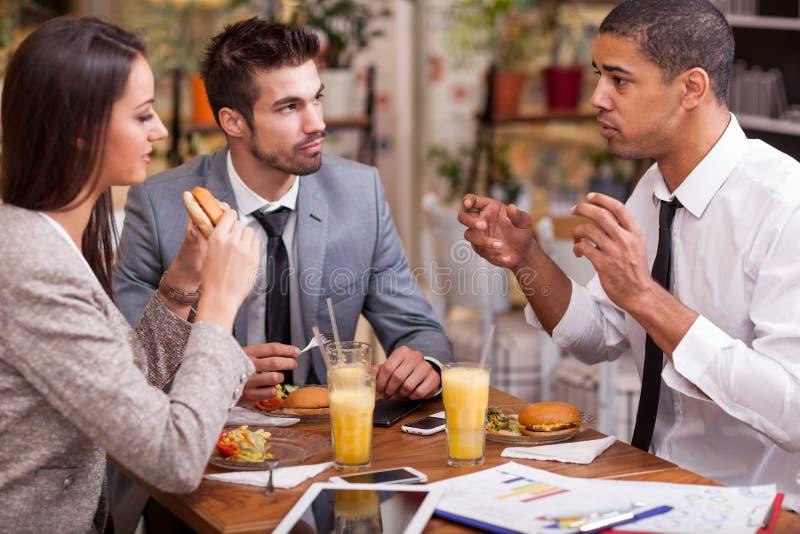 El grupo de hombres de negocios jovenes goza en almuerzo en el restaurante foto de archivo