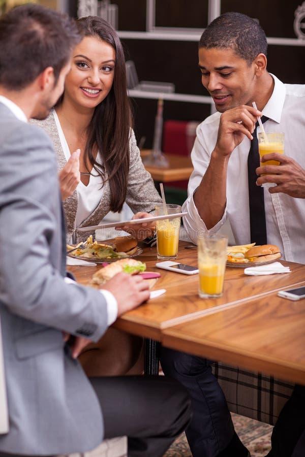 El grupo de hombres de negocios jovenes goza en almuerzo en el restaurante fotos de archivo