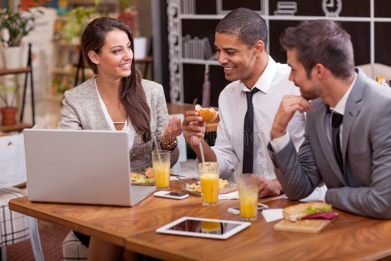 El grupo de hombres de negocios jovenes goza en almuerzo en el restaurante imagen de archivo libre de regalías