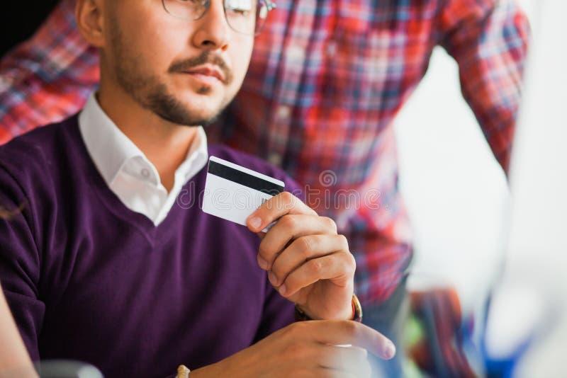 El grupo de hombres de negocios hace compras en l?nea en la oficina foto de archivo