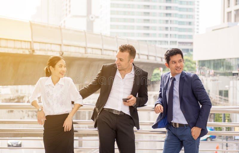 El grupo de hombres de negocios de la diversidad combina hablar y consulta mientras que se une al aire libre imagen de archivo libre de regalías