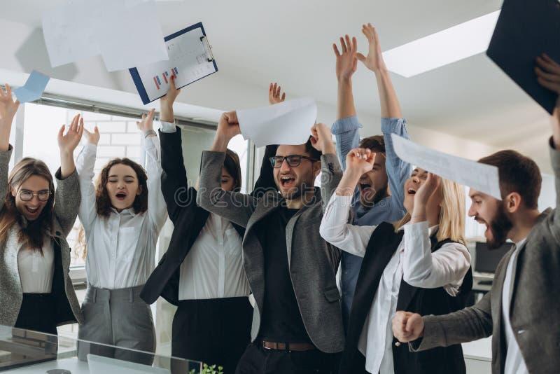 El grupo de hombres de negocios que celebran lanzando sus documentos comerciales y los documentos vuelan en el aire, poder de la  imagen de archivo