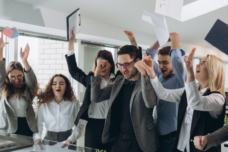 El grupo de hombres de negocios que celebran lanzando sus documentos comerciales y los documentos vuelan en el aire, poder de la  fotografía de archivo