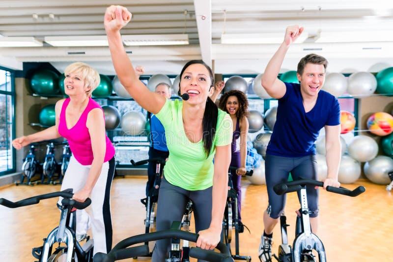 El grupo de hombres y de mujeres que hacen girar en aptitud bikes en gimnasio fotografía de archivo libre de regalías