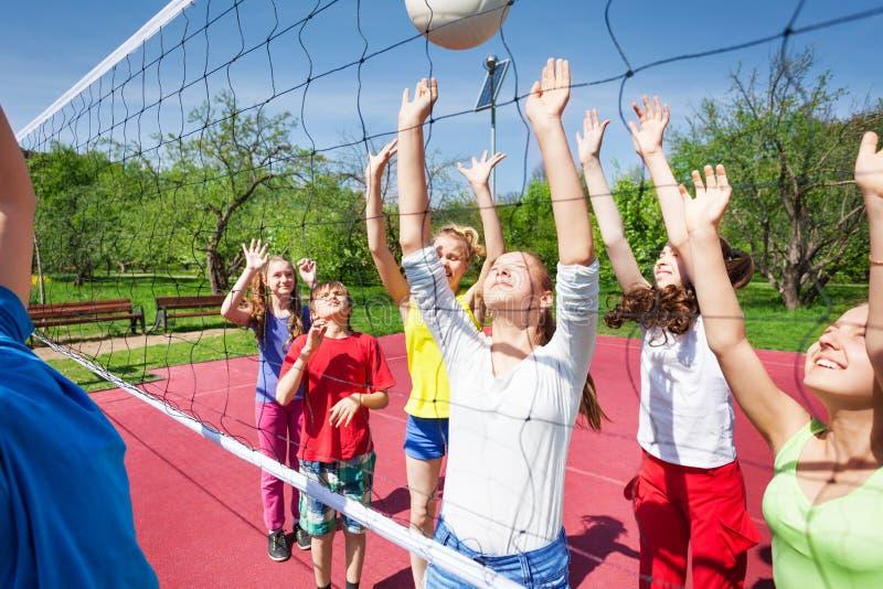 El grupo de jugar adolescencias con los brazos para arriba salta cerca de red imagenes de archivo