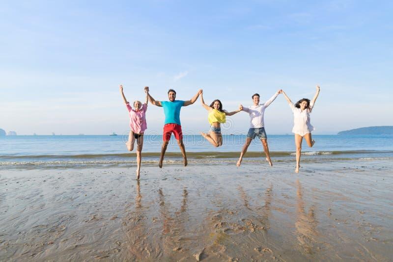 El grupo de la gente joven salta el las vacaciones de verano de la playa, mar sonriente feliz de los amigos imagenes de archivo