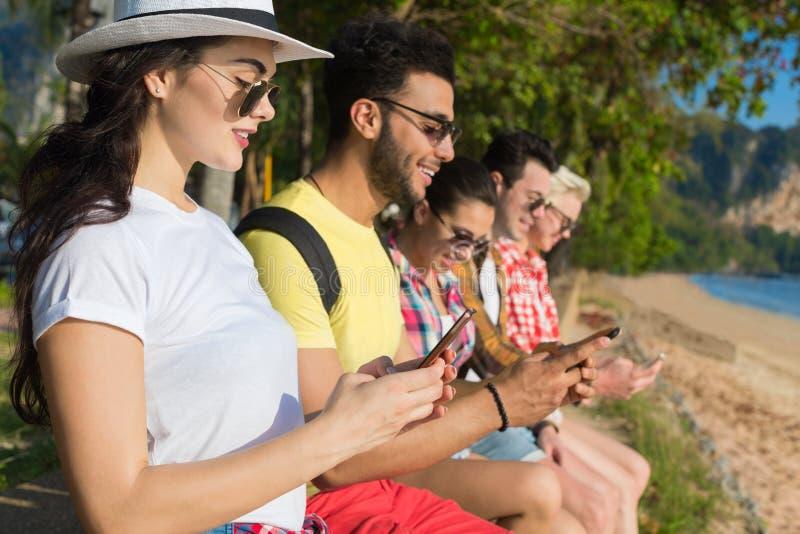 El grupo de la gente joven usando la célula Smart llama por teléfono a los amigos tropicales de las palmeras del parque que charl imagen de archivo libre de regalías