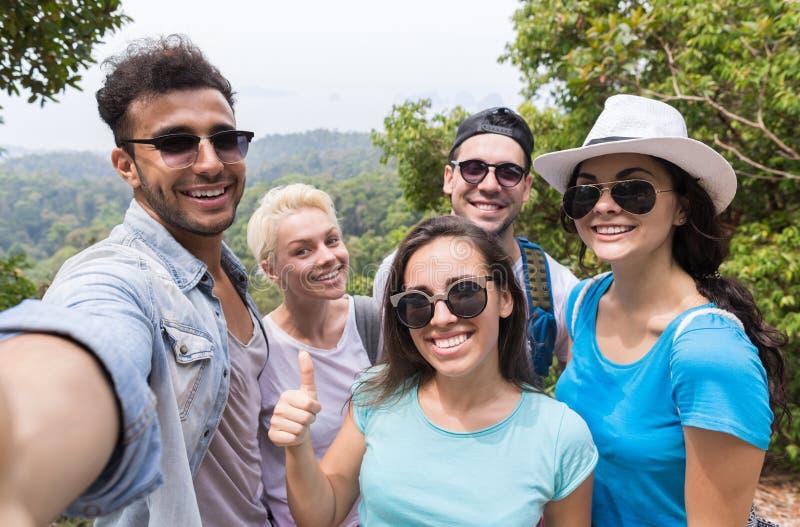 El grupo de la gente toma la foto de Selfie sobre el paisaje hermoso de la montaña, emigrando en el bosque, hombres jovenes de la fotografía de archivo