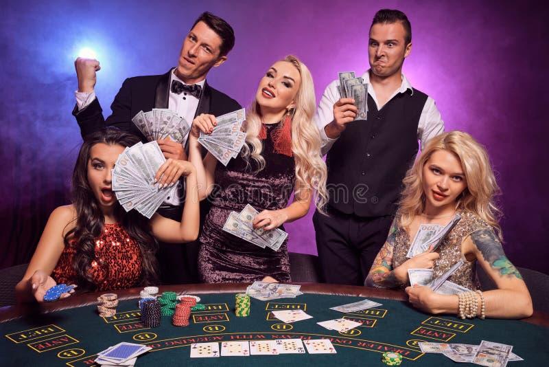 El grupo de los amigos ricos jovenes está jugando el póker en un casino foto de archivo