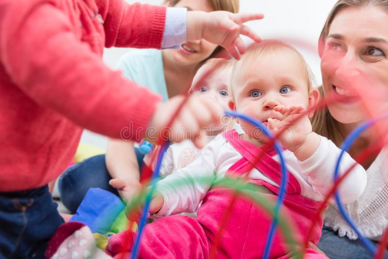 El grupo de madres jovenes felices que miran a sus bebés lindos y sanos juega imágenes de archivo libres de regalías