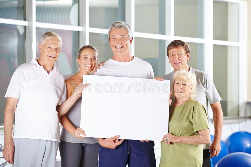 El grupo de mayores sostiene la cartelera en blanco en el centro de aptitud imagen de archivo libre de regalías