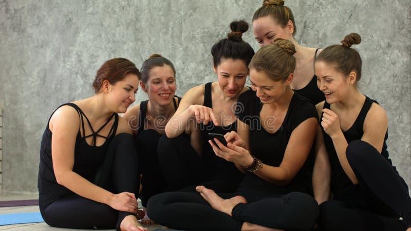 El grupo de muchachas en clase de la aptitud en la rotura que mira el teléfono celular, feliz y sonriendo, muestra la cara divert imagen de archivo libre de regalías
