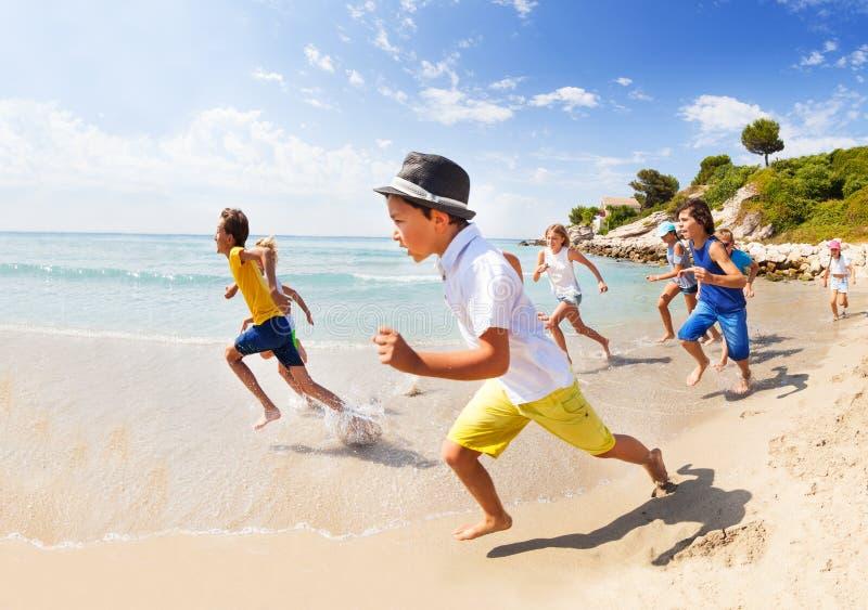 El grupo de muchachos y las muchachas corren a lo largo de la playa del mar fotos de archivo libres de regalías
