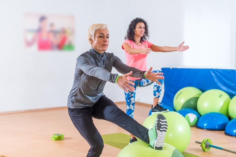 El grupo de mujeres deportivas alegres activas que hacen la sola pierna se pone en cuclillas con la bola de la balanza que entren foto de archivo
