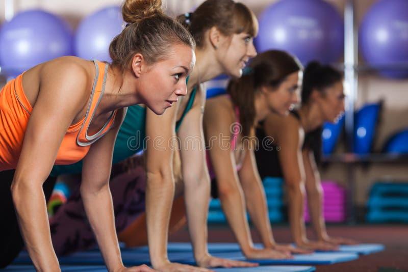 El grupo de mujeres en el gimnasio empuja hacia arriba ejercicio del entrenamiento fotografía de archivo libre de regalías