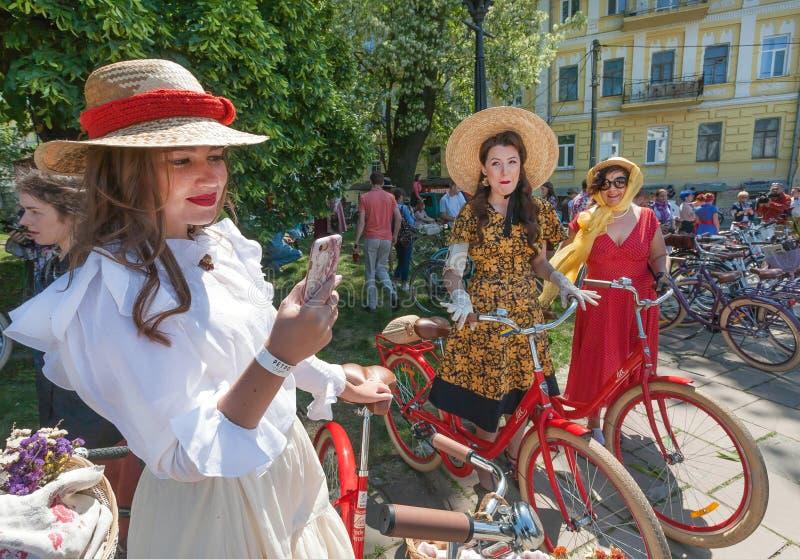 El grupo de mujeres en la vieja moda viste listo para completar un ciclo con la bicicleta del vintage durante travesía retra del  fotografía de archivo libre de regalías