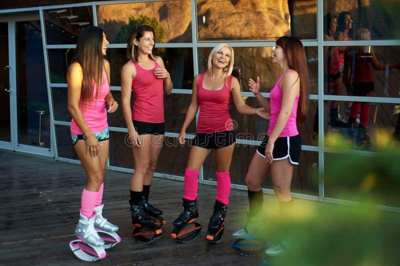 El grupo de mujeres de la aptitud vestidas en ropa de deportes habla antes de entrenamiento de salto del kangoo imagenes de archivo