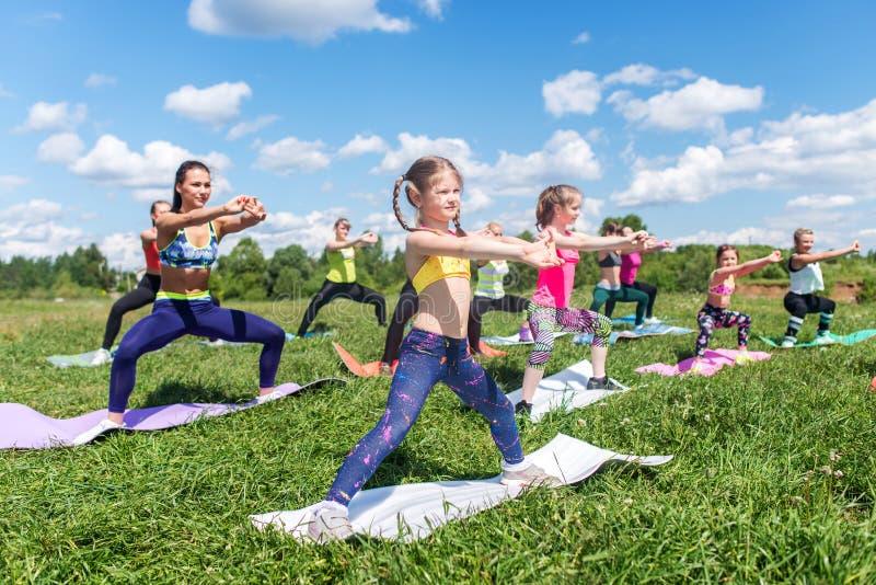 El grupo de mujeres que ejercitan y que hacen se pone en cuclillas en el campo de bota foto de archivo libre de regalías