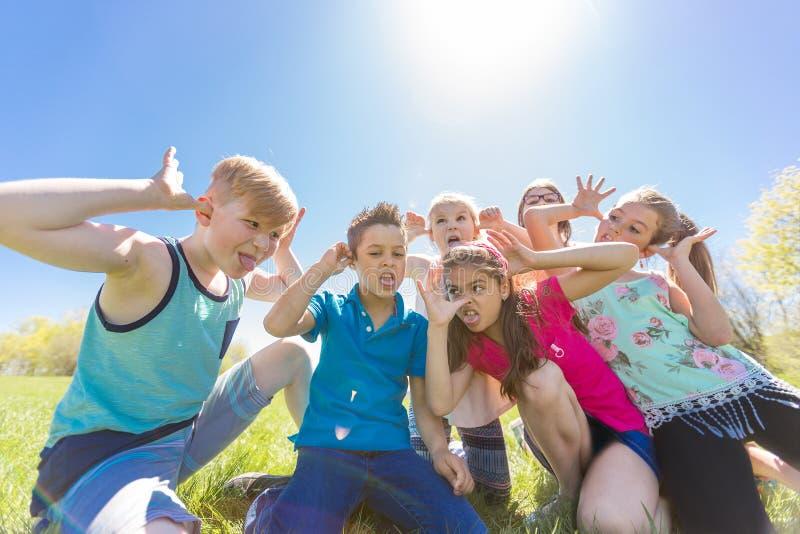 El grupo de niño se divierte en un campo fotografía de archivo