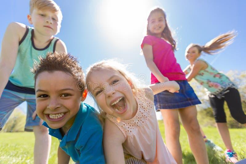El grupo de niño se divierte en un campo imagen de archivo