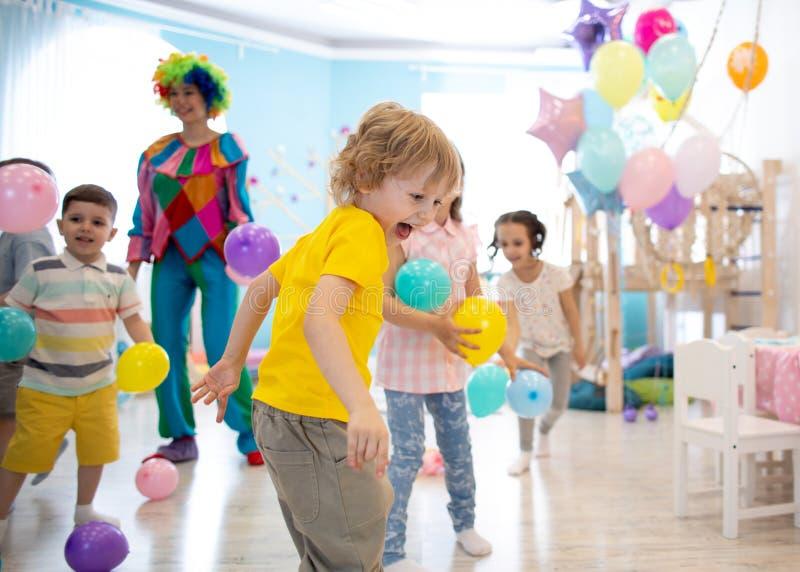 El grupo de niños celebra la diversión del partido junta imagenes de archivo