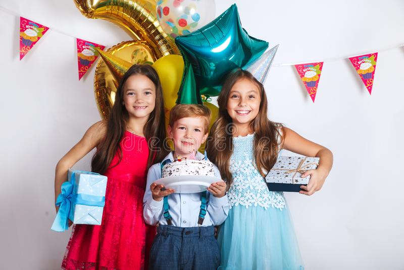 El grupo de niños celebra la fiesta de cumpleaños junto Niños que miran la torta de cumpleaños con las velas fotografía de archivo libre de regalías