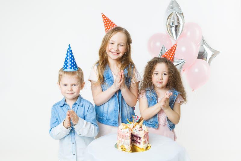 El grupo de niños en casquillos festivos aplaude sus manos cerca de la torta de cumpleaños, globos en fondo foto de archivo libre de regalías