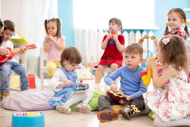 El grupo de niños envejece 3-4 años que juegan los juguetes musicales diversos Educación musical temprana en guardería imagenes de archivo