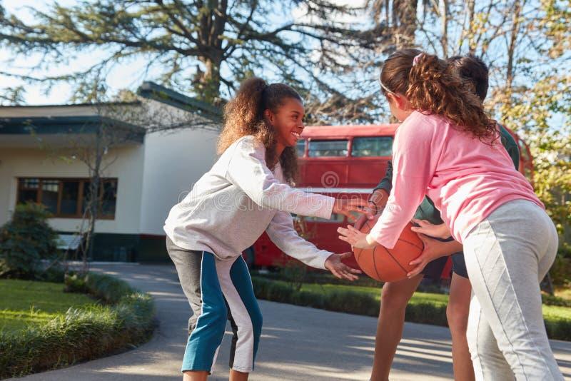 El grupo de niños está jugando a baloncesto durante los días de fiesta imagen de archivo libre de regalías