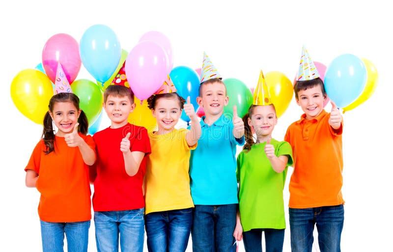 El grupo de niños felices en los sombreros del partido que muestran los pulgares sube la muestra imágenes de archivo libres de regalías