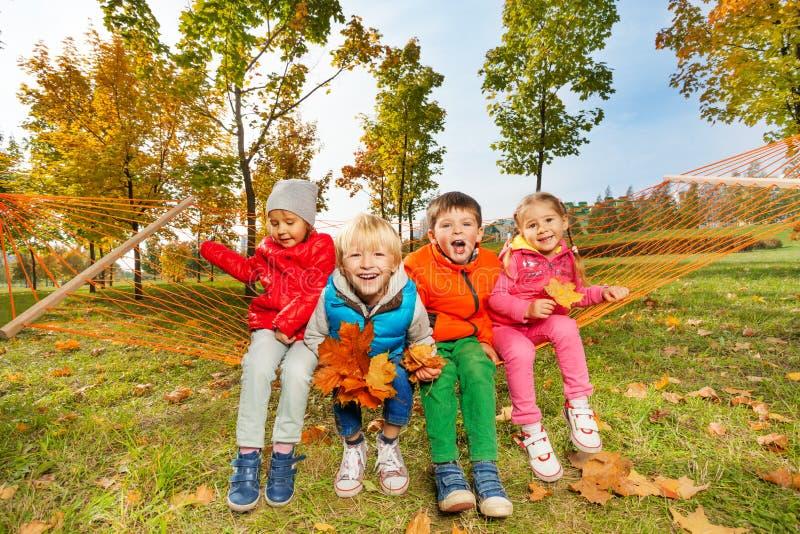 El grupo de niños felices se sienta en la hamaca y goza de ella imágenes de archivo libres de regalías