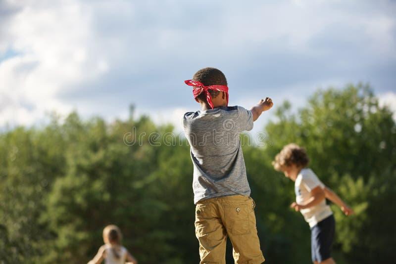 El grupo de niños juega la piel de ante del ` s del hombre ciego fotos de archivo libres de regalías