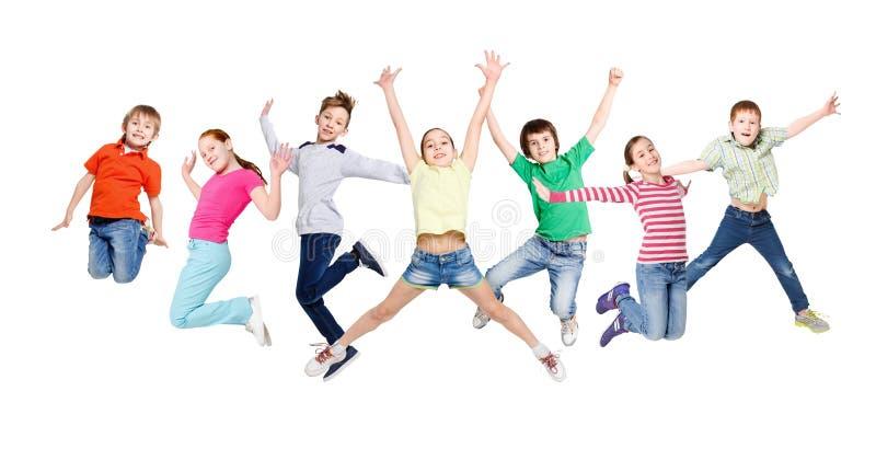 El grupo de niños que saltaban en el blanco aisló el fondo del estudio foto de archivo libre de regalías