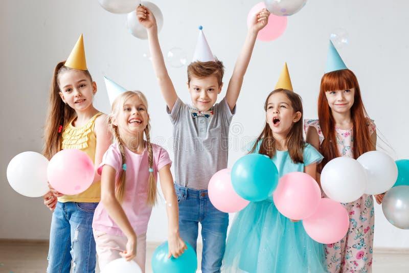 El grupo de pequeños niños tiene fiesta de cumpleaños, lleva los sombreros festivos, sostiene los globos, tiene alegría junta, go imagen de archivo libre de regalías