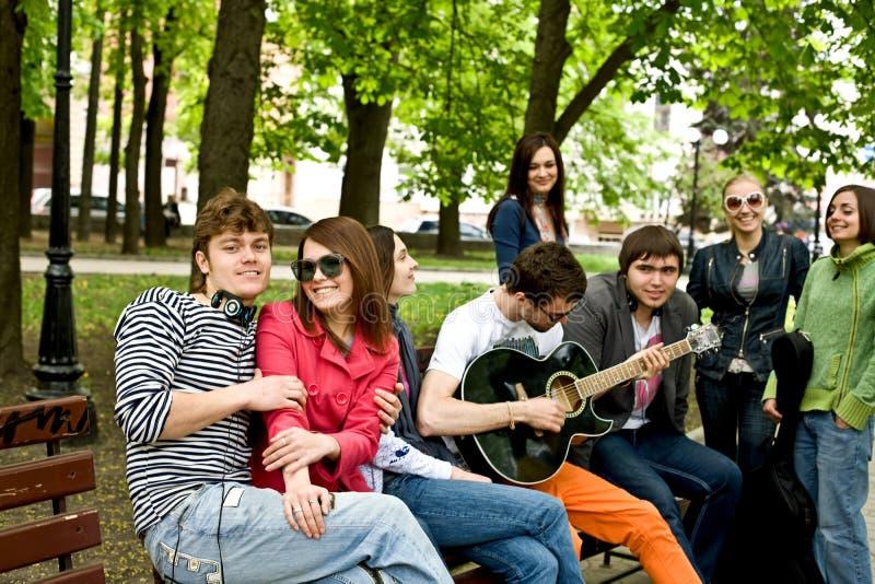 El grupo de personas en parque de la ciudad escucha música. fotos de archivo libres de regalías