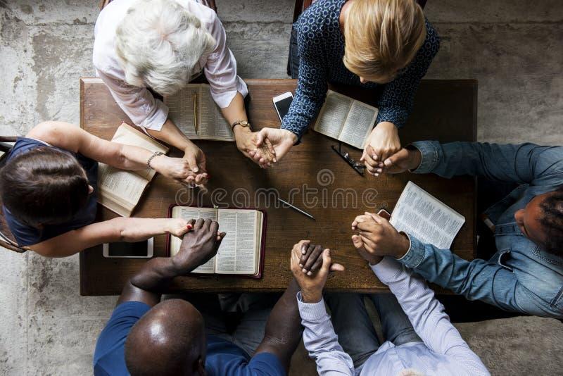 El grupo de personas que lleva a cabo las manos que ruegan la adoración cree imagen de archivo