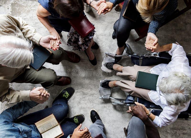 El grupo de personas que lleva a cabo las manos que ruegan la adoración cree fotografía de archivo libre de regalías