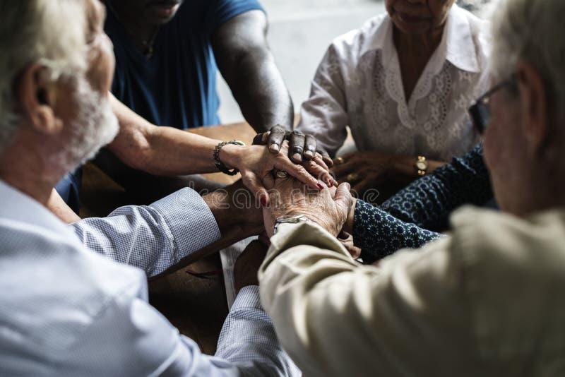 El grupo de personas que lleva a cabo las manos que ruegan la adoración cree imagenes de archivo