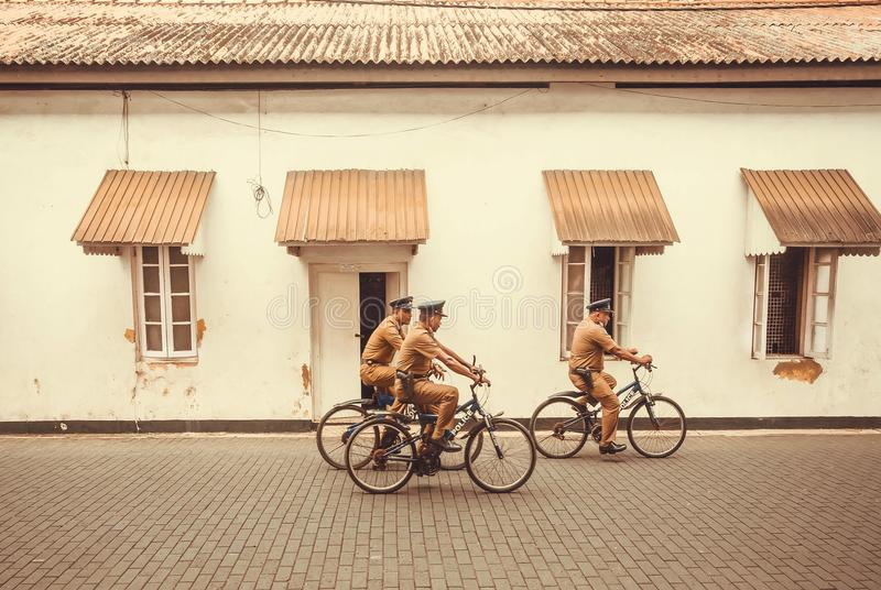 El grupo de policías en el montar a caballo uniforme retro monta en bicicleta en ciudad histórica fotos de archivo