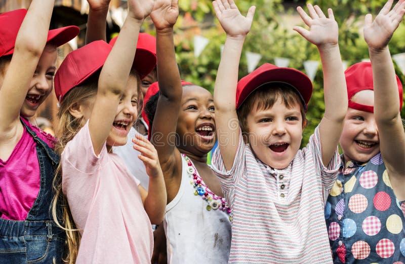 El grupo de sonrisa aumentada mano de la felicidad de los amigos de la escuela de los niños aprende foto de archivo libre de regalías