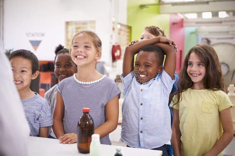 El grupo de sonrisa embroma escuchar el profesor en centro de la ciencia foto de archivo libre de regalías