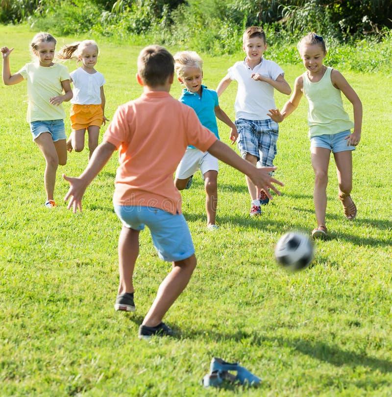 El grupo de sonrisa embroma jugar al fútbol junto en césped verde adentro fotografía de archivo libre de regalías